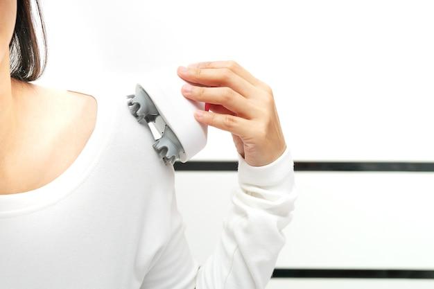 Nek- en schoudermassageapparaat met elektrische arm op de schouder van een vrouw