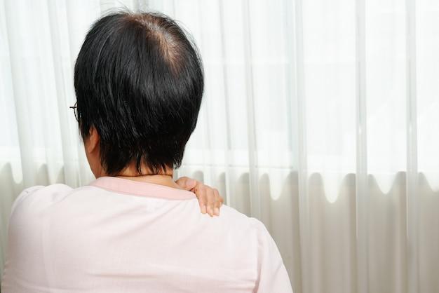 Nek- en schouderpijn, oude vrouw die lijdt aan nek- en schouderletsel, gezondheidsprobleemconcept
