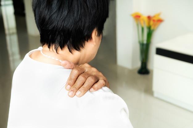 Nek- en schouderpijn, oude vrouw die lijdt aan nek- en schouderletsel