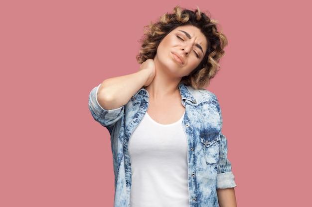 Nek- of rugpijn. portret van een jonge vrouw met krullend kapsel in een casual blauw shirt dat haar pijnlijke nek vasthoudt en zich slecht voelt. indoor studio opname, geïsoleerd op roze achtergrond.