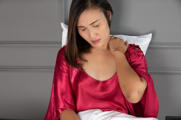 Nekpijn en schouderpijn bij een vrouw, pijn beknelde zenuw in nek of schouder, vrouwen dragen rode nachtjapon en satijnen kamerjas met korte mouwen en bloemenkant met stijve nek bij het ontwaken in de ochtend