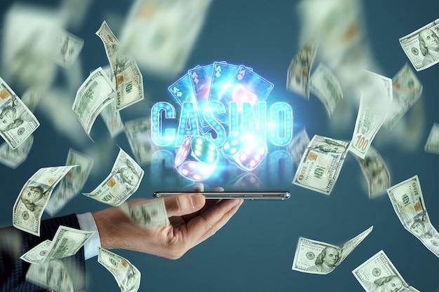 Neon casino-inscriptie, speelkaarten en dobbelstenen over het smartphonescherm en dalende dollars. online casino, gokken, wedden, roulette. flyer, poster, sjabloon voor reclame.