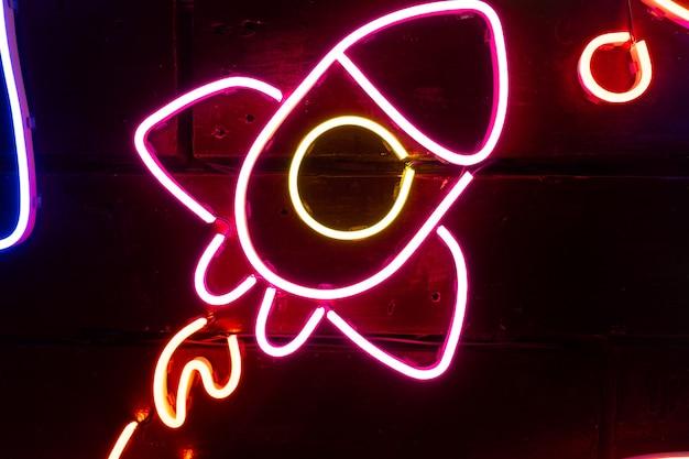 Neon geassorteerde vormen op een zwarte muur.