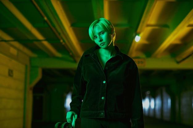 Neon schieten in groene tinten een meisje met kort haar staat op een lege parkeerplaats hoge kwaliteit foto