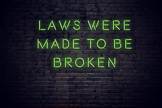 Neoninschrijving van positief wijs citaat tegen bakstenen muur