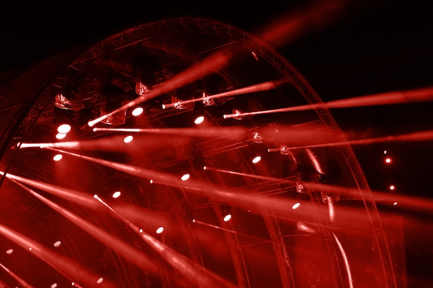 Neonlicht. lichtstralen van concertverlichting op een donkere achtergrond boven het projectiescherm.