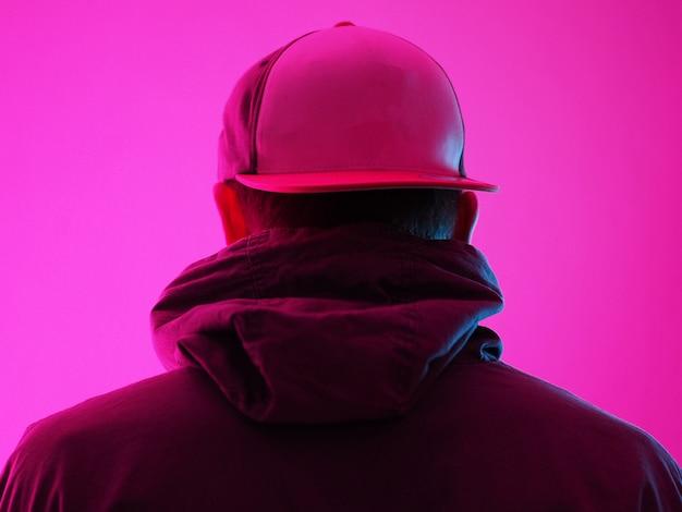 Neonlicht man in hoody. heldere kleurrijke lichteffecten. achteraanzicht