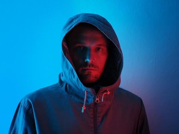 Neonlichtportret van de ernstige mens in hoody. heldere kleurrijke lichteffecten.