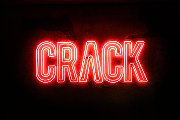Neonteken op een gebroken muur - crack