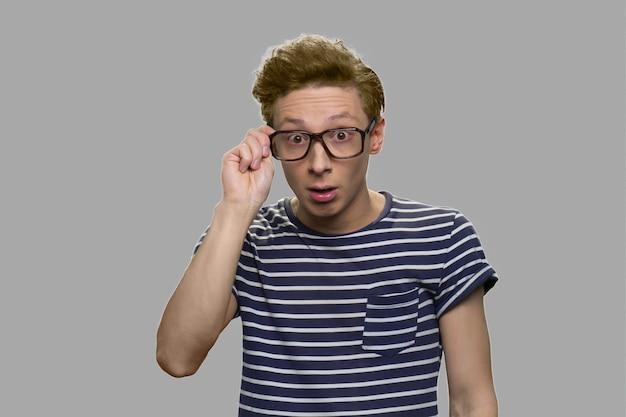 Nerd jongen in bril met verbaasde gezichtsuitdrukking. knappe jonge man in glazen op zoek geschokt. uitvinding, inzicht concept.