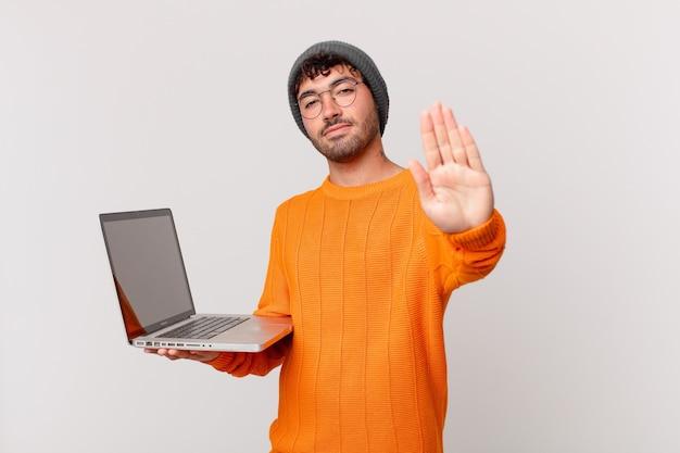 Nerd man met computer die er serieus, streng, ontevreden en boos uitziet en een open hand laat zien die een stopgebaar maakt