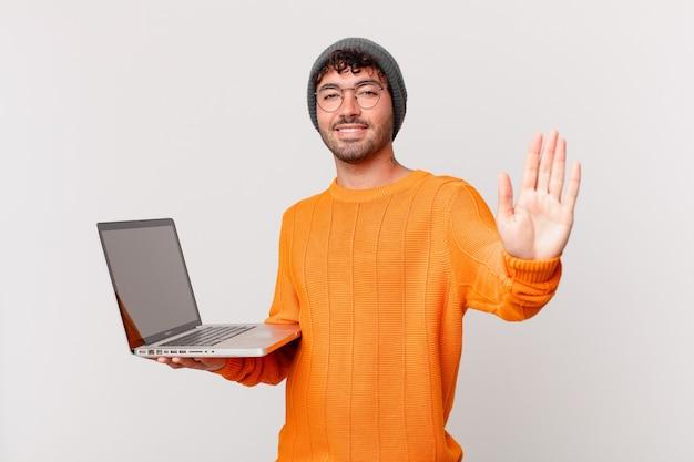 Nerd man met computer die vrolijk en vrolijk lacht, met de hand zwaait, je verwelkomt en begroet, of afscheid neemt