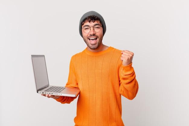 Nerd-man met computer die zich geschokt, opgewonden en gelukkig voelt, lacht en succes viert, en zegt wauw!