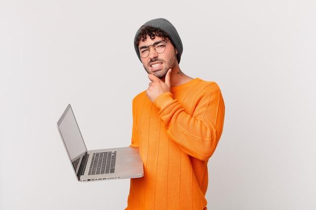 Nerd man met computer met mond en ogen wijd open en hand op kin, onaangenaam geschokt voelen, wat zeggen of wow