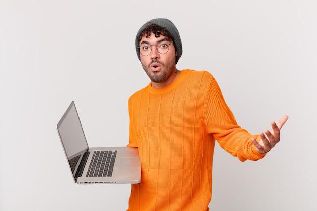 Nerd man met computer met open mond en verbaasd, geschokt en verbaasd met een ongelooflijke verrassing