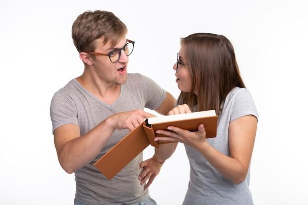 Nerds, studie, mensenconcept. een paar mensen kijken naar het boek en zien er verbaasd uit.