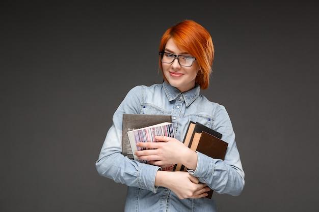 Nerdy roodharige vrouwelijke student draagt boeken