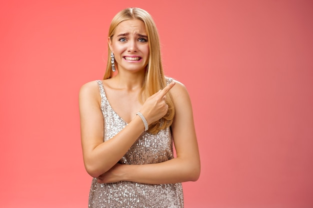 Nerveus aarzelend aantrekkelijke bezorgd blonde vrouw ineenkrimpen fronsen op elkaar geklemde tanden wijzend achter vrienden zoeken hulp zie ex-vriend onwillig om gezien te worden, staande angstig onhandig partij rode achtergrond