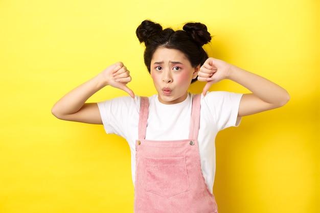 Nerveus aziatisch meisje dat zich slecht voelt, duimen naar beneden laat zien en fronsend verdrietig is, negatieve emotie toont, staande in zomerkleren op geel.