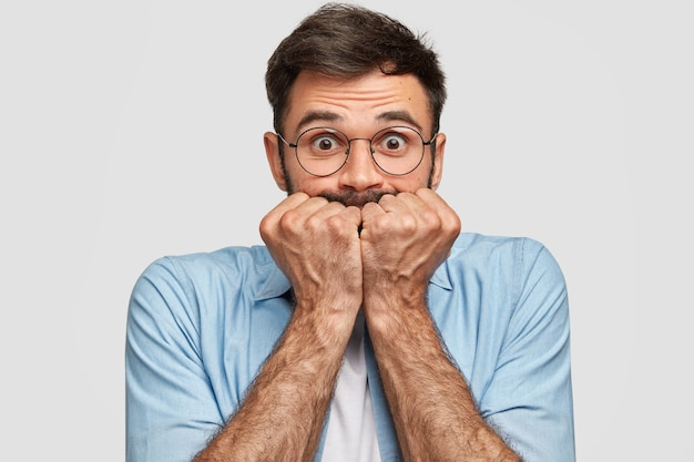 Nerveus bange man houdt vuisten bij de mond, heeft een bezorgde uitdrukking, staart, geïsoleerd over een witte muur. een ongeschoren jongeman voelt zich depressief. mensen en bezorgdheid concept