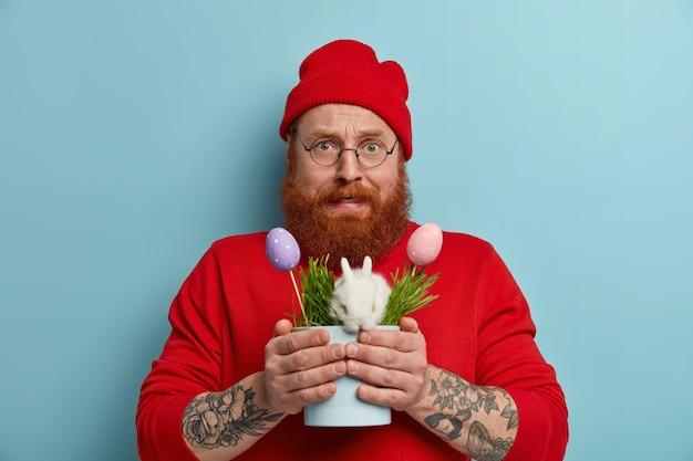 Nerveus bebaarde man bereidt zich voor op de paasviering, houdt een pot met een klein wit konijn en versierde kleurrijke eieren, ziet er verbaasd uit, gekleed in een rode outfit, vormt binnen. lente vakantie