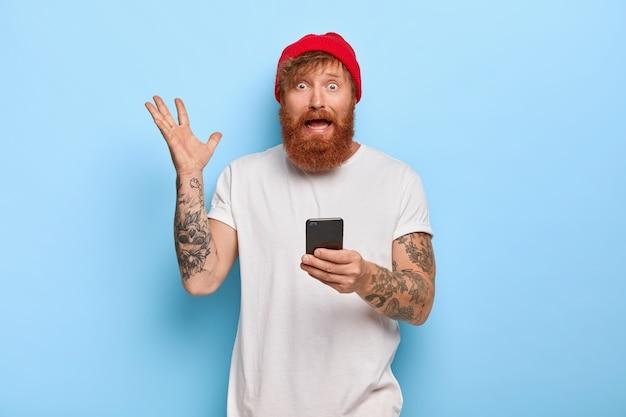 Nerveus bezorgd, bebaarde gember man steekt hand op, houdt mobiele telefoon vast, draagt een rode hoed en een wit t-shirt, gebruikt moderne technologie, voelt zich perpelex en onrustig, controleert de rekeninglijst online, gebaart boos