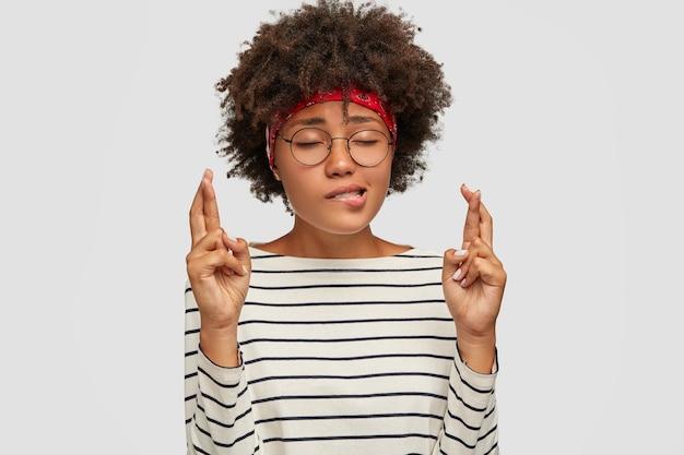 Nerveus bijgelovige jonge vrouw bijt op de lippen