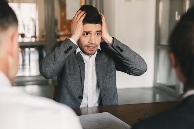 Nerveus gespannen man 30s zorgen maken en zijn hoofd grijpen tijdens sollicitatiegesprek op kantoor, met collectief van specialisten - bedrijfs-, carrière- en wervingsconcept