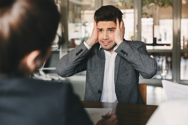 Nerveus gespannen mannelijke kandidaat 30s zich zorgen maken en zijn hoofd grijpen tijdens sollicitatiegesprek op kantoor, met groep managers - bedrijfs-, carrière- en rekruteringsconcept