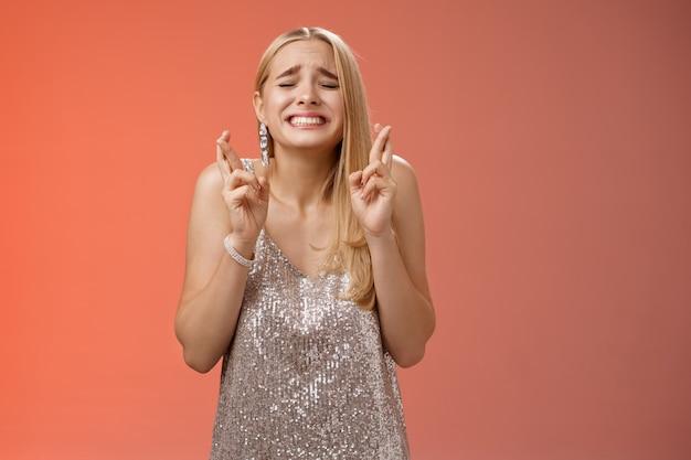 Nerveus hoopvolle blonde jonge vrouw in zilveren trendy jurk sluit ogen grimassen gretig wens uitkomen kruis vingers veel geluk bidden smekend anticiapting fortuin, staande bezorgd rode achtergrond.