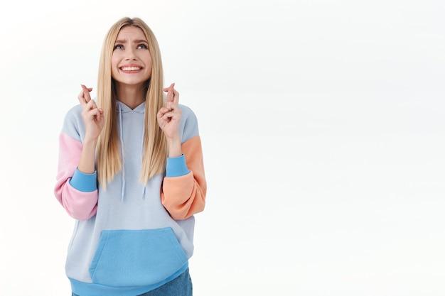 Nerveus meisje dat zich angstig voelt over de resultaten van het examen, vingers gekruist veel geluk, tanden op elkaar klemmen en loensen terwijl ze naar de lucht kijkt