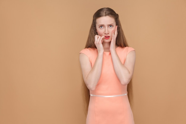 Nerveus ongelukkig verward meisje dat naar de camera kijkt en nagels bijt. emotionele schattige, mooie vrouw met make-up en lang haar in roze jurk, studio opname, geïsoleerd op lichtbruine of beige achtergrond.