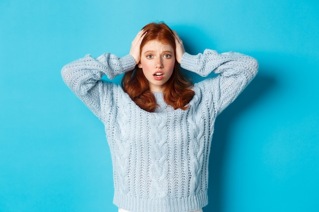 Nerveus roodharig meisje staat overweldigd, houdt handen in paniek op het hoofd en staart naar de camera, staat angstig tegen een blauwe achtergrond.