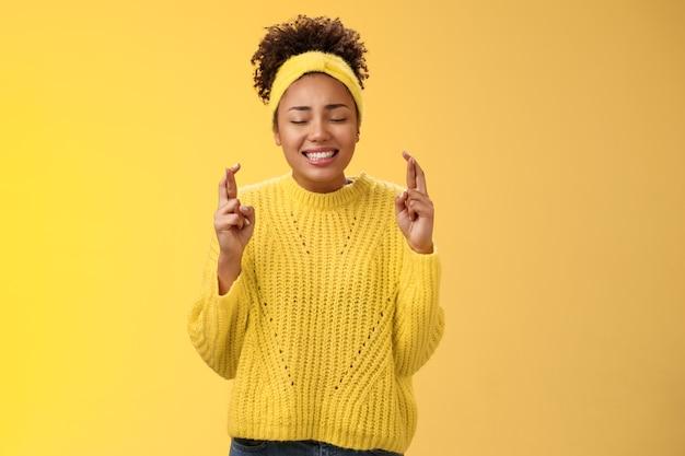 Nerveus trouw intens afro-amerikaans meisje sluit ogen kruis vingers veel geluk bidden wens doen vragen god hulp droom die uitkomt, hopelijk anticiperend op wonder goede positieve resultaten.