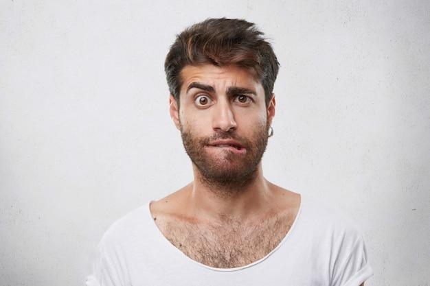 Nerveus twijfelachtig mannetje met stijlvol kapsel en baard die zijn wenkbrauw fronst, bijtende lippen die een verbaasde blik hebben en een serieuze beslissing gaan nemen. verrast macho man uiting geven aan zijn gevoelens en emoties
