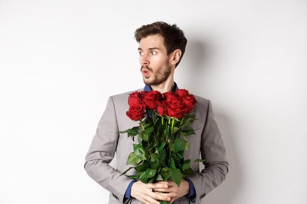 Nerveus vriendje wacht op zijn date op valentijnsdag, kijkt verbaasd links, met boeket rode rozen, staande in pak op witte achtergrond.