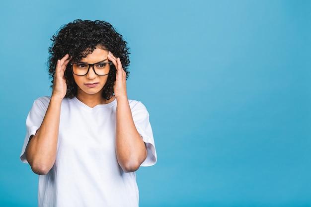 Nerveuze afrikaanse vrouw ademhaling kalmeren verlichten hoofdpijn of omgaan met stress, zwart meisje gevoel gestrest masseren tempels uitademen geïsoleerd op blauwe achtergrond.