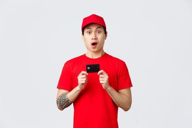 Nerveuze aziatische bezorger in rood t-shirt en petuniform, creditcard vast, camera starend en naar adem snakkend. jonge koeriers raden aan om contactloos betalen te gebruiken voor aankopen in zelfquarantaine