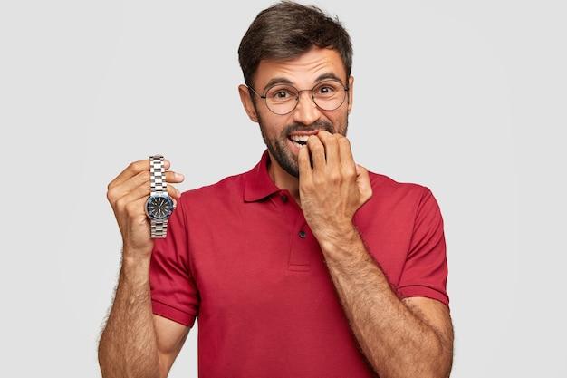 Nerveuze bebaarde man bijt vingernagels, houdt polshorloge vast, maakt zich zorgen als te laat voor een belangrijke vergadering, gekleed in een casual t-shirt. een verlegen jongeman wacht ergens op. de tijden vliegen snel