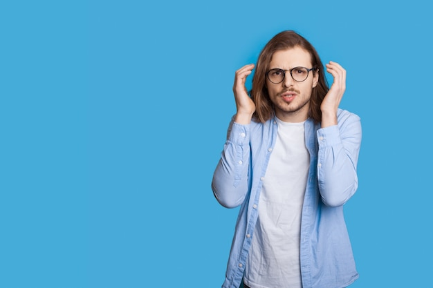 Nerveuze blanke man met lang haar en baard in vrijetijdskleding is poseren op een blauwe muur met vrije ruimte gebaren pijn en agressie
