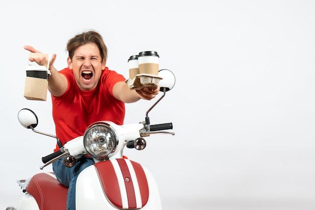 Nerveuze emotionele koeriersmens in rood uniform zittend op motorfiets die bestellingen op witte achtergrond levert