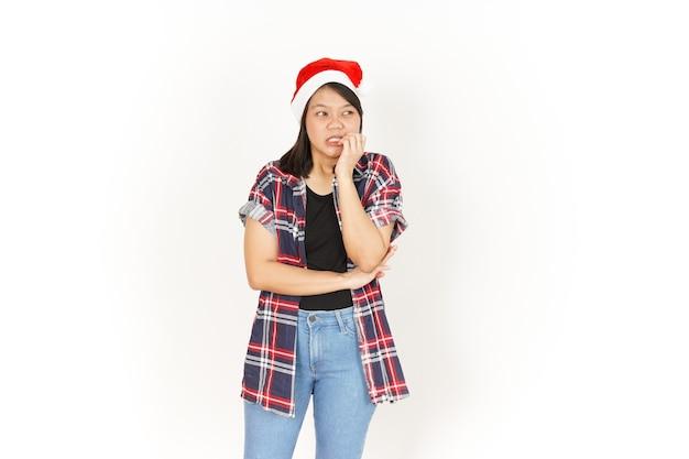 Nerveuze en bijtende nagel van mooie aziatische vrouw met rood geruit hemd en kerstmuts