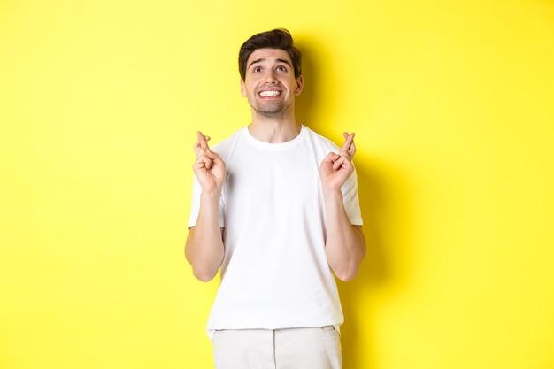 Nerveuze en hoopvolle man die tot god bidt, wens doet met gekruiste vingers, in paniek raakt en over gele achtergrond staat