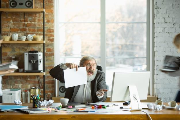 Nerveuze en vermoeide baas op zijn werk bezig terwijl mensen in de buurt wazig zijn. beambte, manager aan het werk, heeft problemen en een deadline, zijn collega's leiden af. bedrijfs-, werk-, werklastconcept.