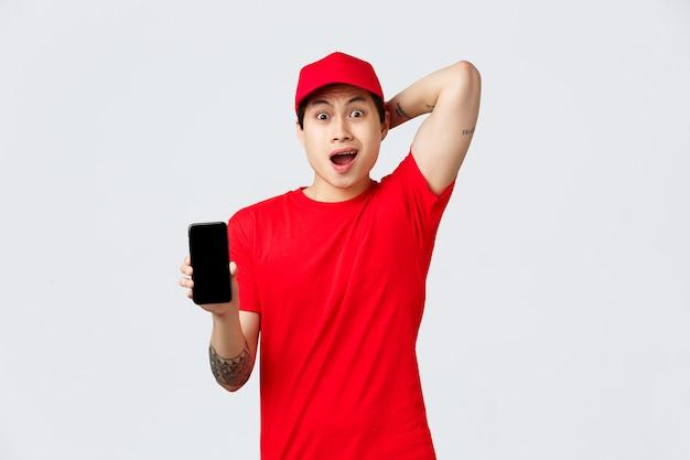 Nerveuze en verontruste aziatische bezorger in rode pet en t-shirt uniform, hijgend angstig, kijken verward en verbaasd met slecht nieuws op het smartphonescherm, verwarde bestelling, grijze achtergrond staan