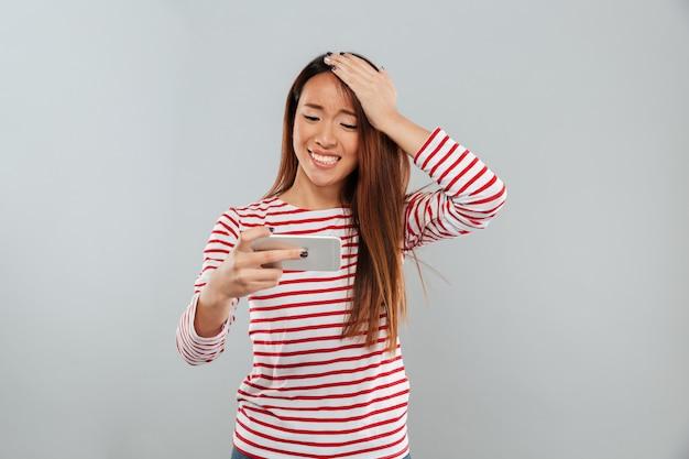 Nerveuze jonge aziatische dame speelt telefonisch spelletjes