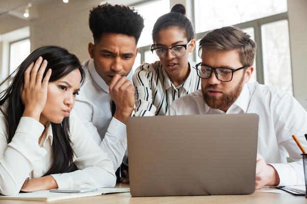 Nerveuze jonge bedrijfscollega's die laptop computer met behulp van.
