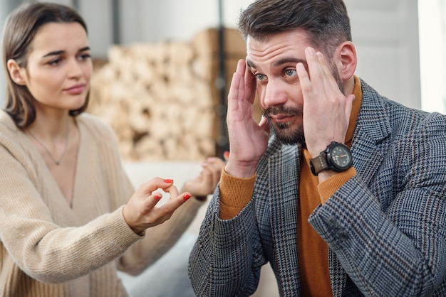 Nerveuze jonge man die probeert niet te luisteren naar zijn vriendin in de slaapkamer.