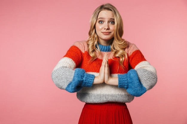Nerveuze jonge mooie mooie vrouw poseren geïsoleerd over roze muur maak alsjeblieft een gebaar