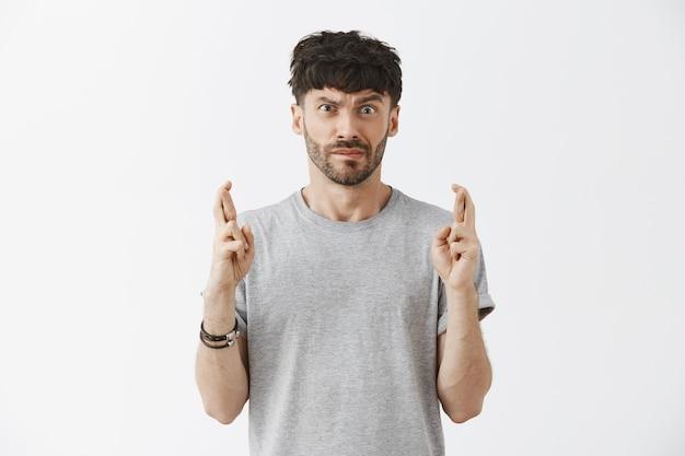 Nerveuze knappe kerel die tegen de witte muur poseert